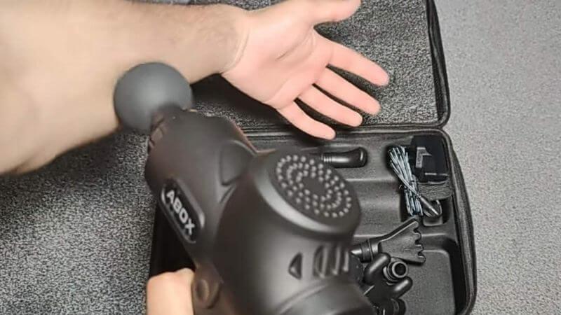 pistola de masaje abox masajeando un brazo